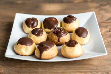 calorie rich food: cheese profiteroles with chocolate on wooden table