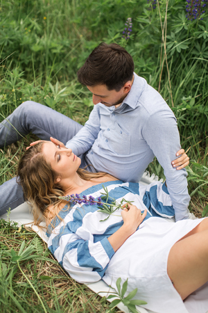 young woman lying on lap of young guy on nature