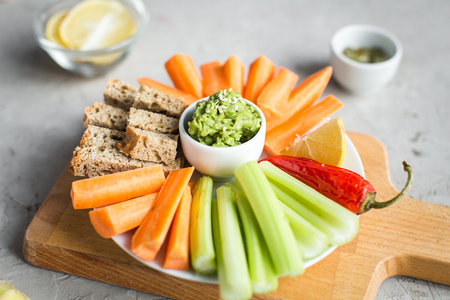 vegan healthy snacks: guacamole, carrots, celery and sesame