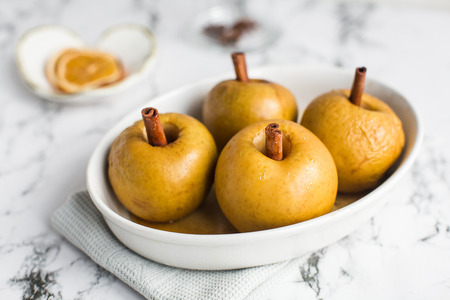 baked apple with cinnamon stick, rum and honey Stock Photo