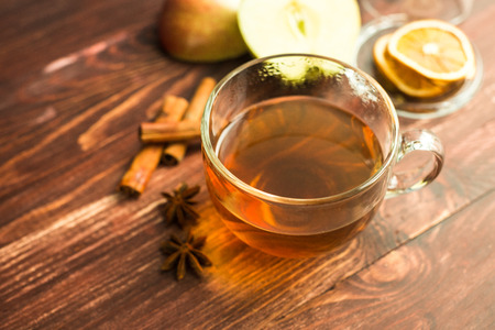 cup of tea on wooden background with cinnamon, anise stars and apple