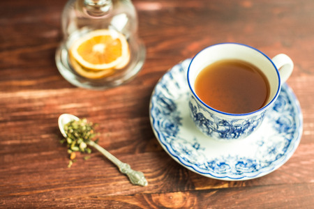 cup of tea on wooden background and tea leaves in spoon Stock Photo
