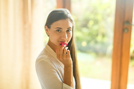 young girl in a white robe in the hotel stands at the window Stock Photo