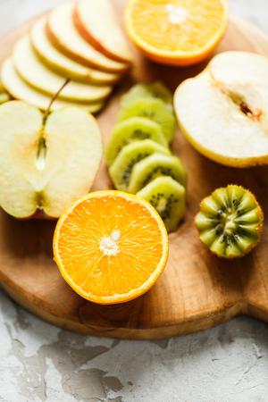 Assorted fruit on board. Apples, Kiwi, pear and orange