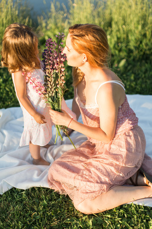 Mother and daughter are sitting on rug by the lake