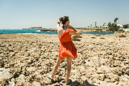 girl in a red dress on the shore of the Mediterranean Sea Stock Photo