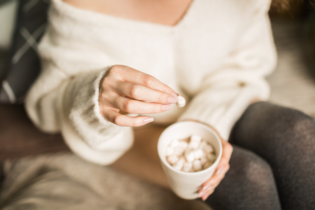 beautiful girl sits on a plaid with a cup of cacao and marshmallows near the bed in the bedroom Stock fotó