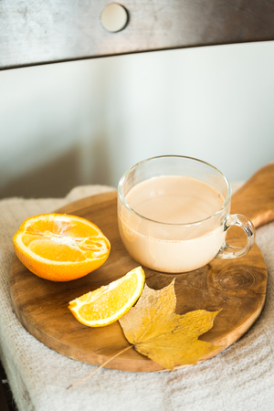 cup of carob with oranges on a wooden board