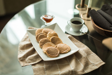 pancakes on white plate with strawberry jam and coffee Stock Photo