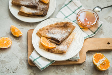 Russian national cuisine, Russian pancakes with orange and honey, top view