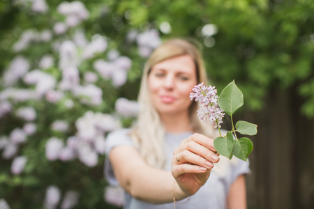 girl holding a sprig of lilac Stock Photo