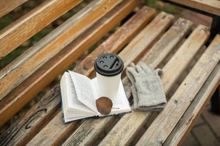 still life: a book and a glass of coffee in the park on a bench