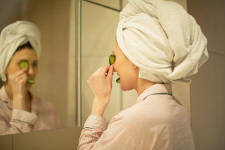 woman with a towel on her head looks in the mirror makes a face mask of cucumbers in the bathroom, home facial treatment, spa