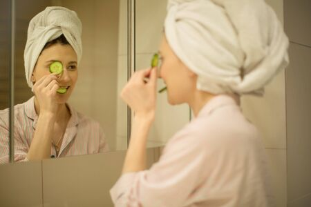 a woman with a towel on her head looks in the mirror makes a face mask from cucumbers in the bathroom, take care of her face for beauty, spa Stockfoto