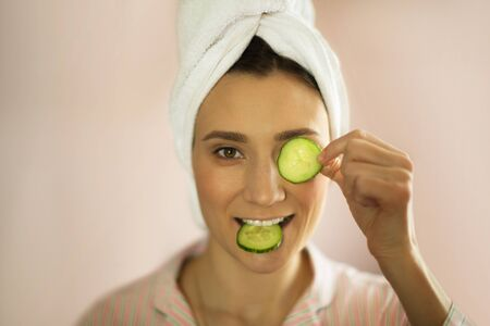 woman with a towel on her head makes a face mask of cucumbers, home facial treatment, spa