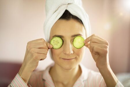 woman with a towel on her head put slices of cucumbers on her eyes, home spa concept