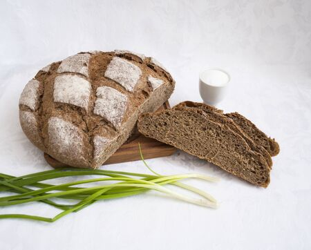 black rye flour bread with spring onions, feathers and salt in a white salt shaker on the table