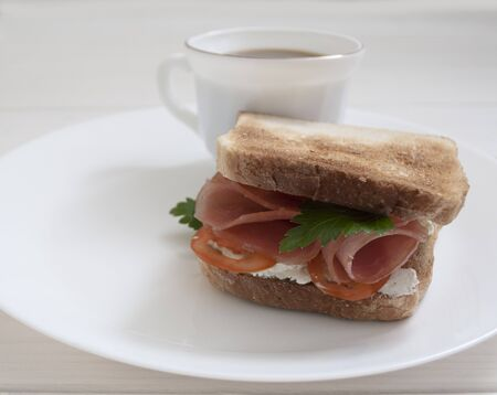 sandwich with sausage and tomatoes on a white plate with a cup of coffee