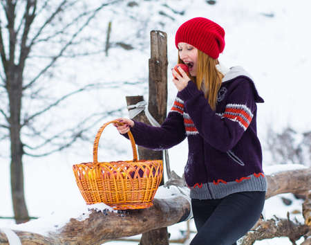 The beautiful blonde girl in red hat in the forest. Girl in winter. White snow. Zdjęcie Seryjne