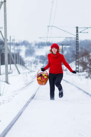 The beautiful blonde girl in red hat in the forest. Girl in winter. White snow. Little Red Riding Hood.