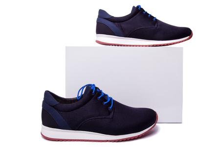 czarno-niebieskie męskie buty sportowe w pobliżu białego pola. Wyizoluj na biały.