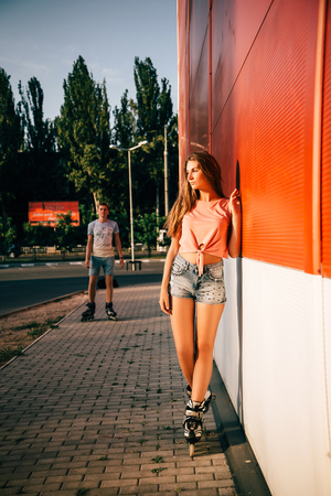 Beautiful couple in love drive rollerblading on the background of a red wall at sunset.  woman waiting man.