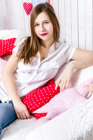 red sofa: Beautiful girl dressed in jeans and a white shirt on a white sofa with pillows in the shape of hearts. The concept of Valentines Day and Love
