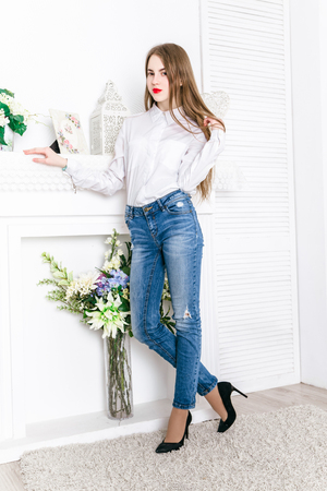 Interior room: Beautiful girl dressed in a shirt and jeans posing in studio interior light