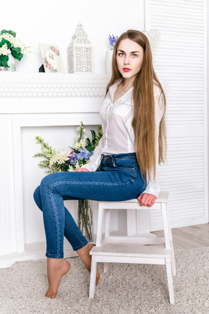 Beautiful girl dressed in a shirt and jeans posing in studio interior light