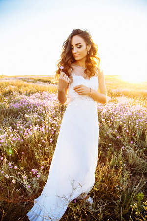 Young happy woman in wedding dress outdoors. beautiful bride in a field at sunset