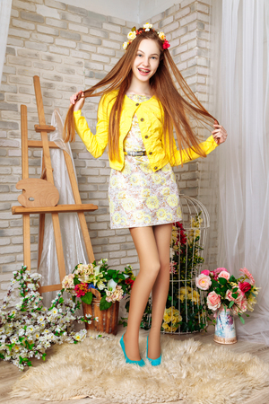 beautiful little girl with perfect makeup and hair-dress in interior studio. Dressed in a white dress and yellow jacket, bright blue shoes Stock Photo