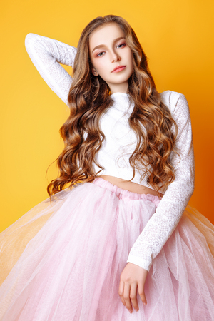 beautiful teenage girl with long curly hair on a yellow background. Dressed in a white sweater and pink tulle full skirt