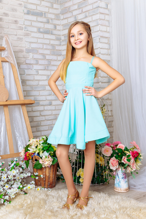 beautiful little girl with perfect makeup and hair. Dressed in a blue dress Stock Photo