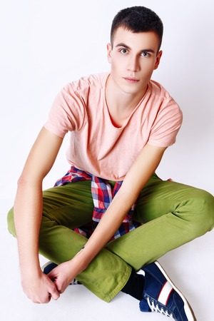 stitting: Attractive trendy young man dressed in pink t-shirt, red plaid shirt and green pants stitting on white background. Studio photo.