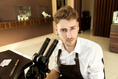 Portrait of a beautiful upset man. Jeweler in the workplace at the table with tools