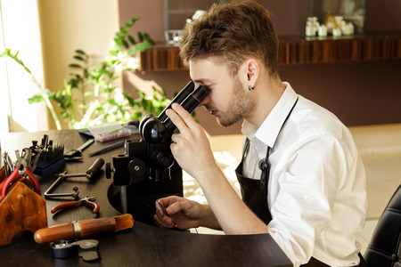 diamond ring: A handsome male jeweler carefully examines through a stone microscope to create a ring. Jewelry repair shop.