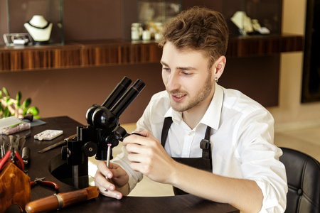 handsome guy jeweler examines a pink gemstone through a magnifying glass in the process of creating a piece of jewelry in the workshop