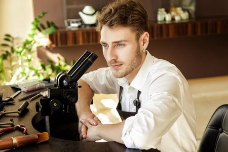 Portrait of a handsome male jeweler sitting at a table with instruments in a jewelers shop