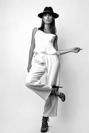 Posing gorgeous emotional girl in a white suit and black hat in the studio on a white background. Black and white photo Stock Photo