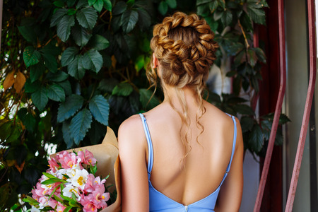Beautiful girl with an open back and gorgeous hairstyle stands on the street holding a bouquet with flowers Stock Photo