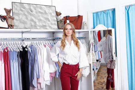 belle fille blonde habillée dans une chemise blanche et pantalon rouge posant dans un magasin de papier. le concept de shopping
