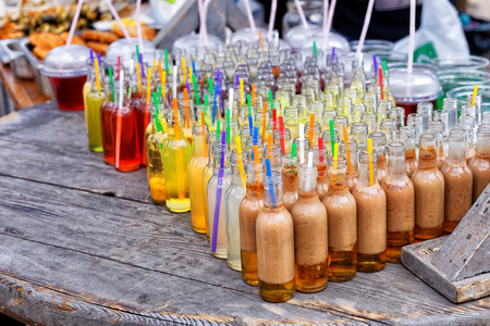 sold small: Festival of street food. Wooden counter with various small bottles with alcoholic and fruit drinks and cocktails sold outdoors in the local market Stock Photo