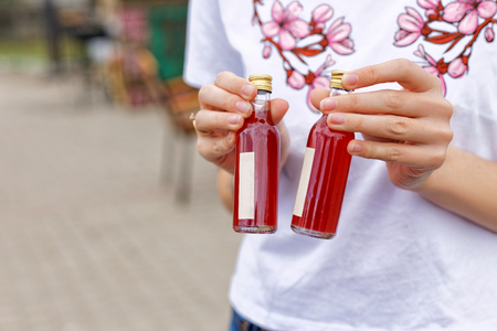 Festival of street food. A girl in a white T-shirt bragging about buying a drink holding small bottles in the open air in the local market. Stock Photo