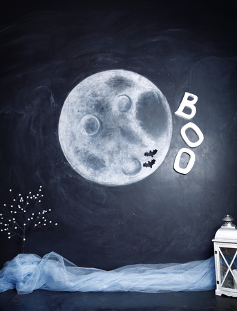 Studio decorated with Halloween location. An image of a full moon on a black background painted with chalk, a blue cloth and a lantern. Stock Photo