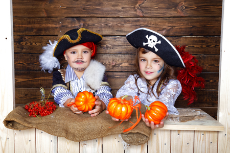 A cheerful boy and girl in pirate costumes play pumpkins near the wooden wall in the studio with Halloween decorations
