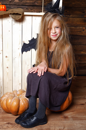 little girl dressed as a witch sits on a pumpkin on the background of the wooden wall in the Studio with decorations for Halloween Stock Photo