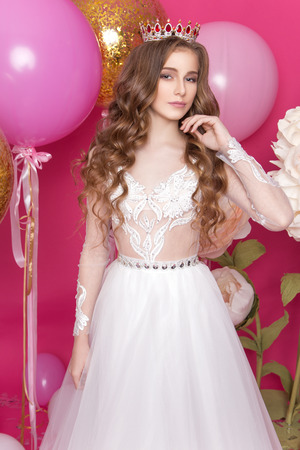 A young teenage girl stands in the studio amid balloons and flowers in a sumptuous white dress and a magnificent crown. Princess with long wavy hair. Queen beauty contest Stock Photo