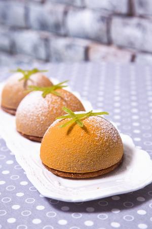 Mini mousse pastry dessert covered with yellow chocolate velour and decorated with powdered sugar. Modern european cake. French cuisine