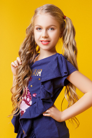 Beautiful little blonde girl with long wavy hair in a fashionable blue t-shirt and jeans posing in studio on a yellow background Archivio Fotografico