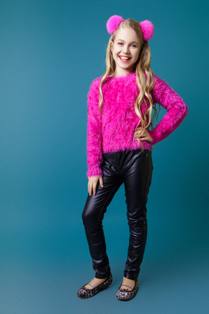 Beautiful little blonde girl with long wavy hair in a funny fluffy pink sweater and tights posing in studio on a blue background